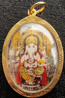 Ganesh image amulet in gold oval case from Thailand.