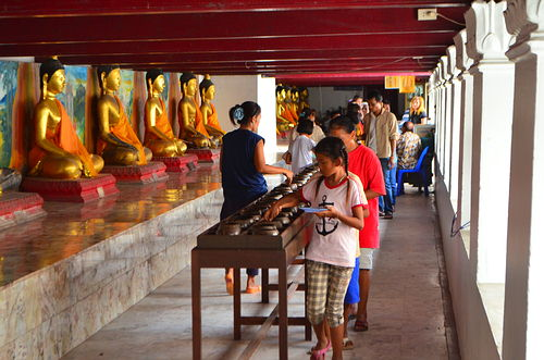 Buddhists giving donations in jars near row of golden Buddha statues.