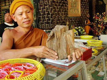 A young Theravada Buddhist monk at Buddhist Temple, Wat Lahn Kuat, holding a block of brown petrified wood - millions of years old. This is the same wood our Somdej Toh amulets are made out of.