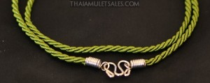 A small olive green Thai amulet necklace for children.