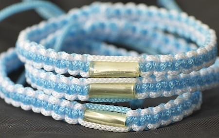 This is a bright colored light blue and white blessed Theravada Buddhist bracelet with adjustable strings to fit most adult and childrens wrists.