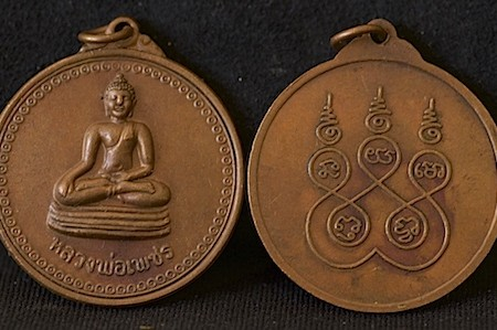 Small, round bronze (brown) Thai amulet featuring Buddha sitting in meditation.