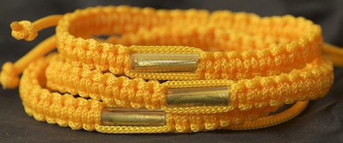 This gold bracelet is also a traditional color for Buddhist bracelets in Thailand. We see this one often, it is quite popular.