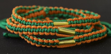 Adjustable nylon cord orange and green blessed Buddhist bracelet with takrud scroll rolled up inside and adjustable straps.