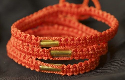 An adjustable traditional orange colored bracelet from the Wat Gaew Temple in Southern Thailand.