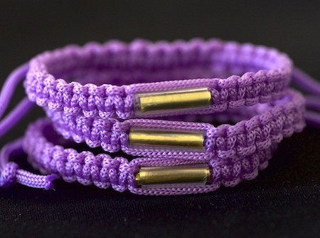 This is a bright purple bracelet that is adjustable and made from nylon cord woven by the monks or magee at the Wat Tum Sua temple.