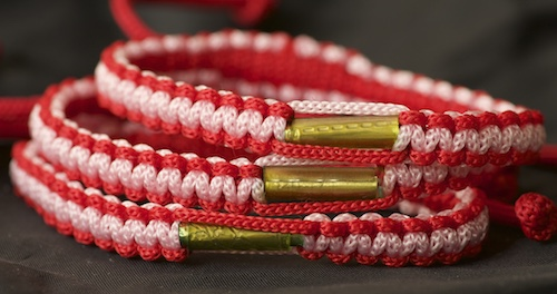 A blessed Theravada Buddhist bracelet woven with nylon and with a takrud scroll attached.
